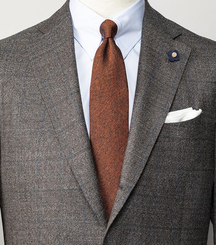 <p><strong>ブラウンスーツで老けて見えないコツは?</strong></br>ミドルエイジのブラウンスーツはともすると老けて見えることもあるが、爽やかなブルーチェックが入ったこんなブラウンスーツなら渋さ加減がちょうどいい。シャツはスーツの柄色と同系色のサックスブルー、ネクタイはスーツの地色と同系色のテラコッタブラウンを選んで、胸元を明るい色で構成すれば顔映りもよくなる。<br /> <small>スーツ16万8000円/ラルディーニ、 シャツ3万4000円/バルバ、ネクタイ2万9000円/キートン(以上ストラスブルゴ) チーフ<スタイリスト私物></p> <p></small></p>