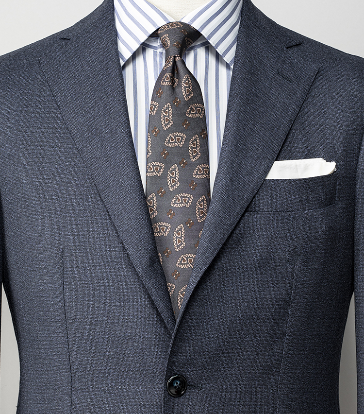 <p><strong>無地スーツで若手社員より貫禄を出すには?</strong></br>グレーにもネイビーにも見える発色が美しいグレイッシュネイビーのスーツは、無地でも織り柄入りで一工夫されているため、若手社員としっかり差をつけられる。シャツはスーツと同系色のネイビーストライプで調和させて、ネクタイはクラシックなペイズリー柄を選択。色柄で多用しなくても、年齢相応の風格を出せる好例だ。<br /> <small>スーツ13万円/バルバ、シャツ5万9000円/フライ、ネクタイ2万5000円/アット ヴァンヌッチ(以上ストラスブルゴ) チーフ<スタイリスト私物></p> <p></small></p>