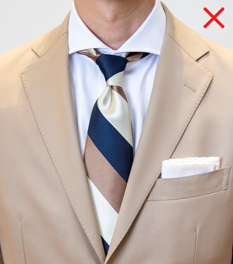 <p>NG例。ネクタイの結び目がゆるく、だらしなくぶら下がっている状態はいただけない。また、楽だからといってシャツの第1ボタンを外してしまっては、いくらネクタイを締めても襟元が歪み、気持ちのたるんだ印象になるので要注意。</p>