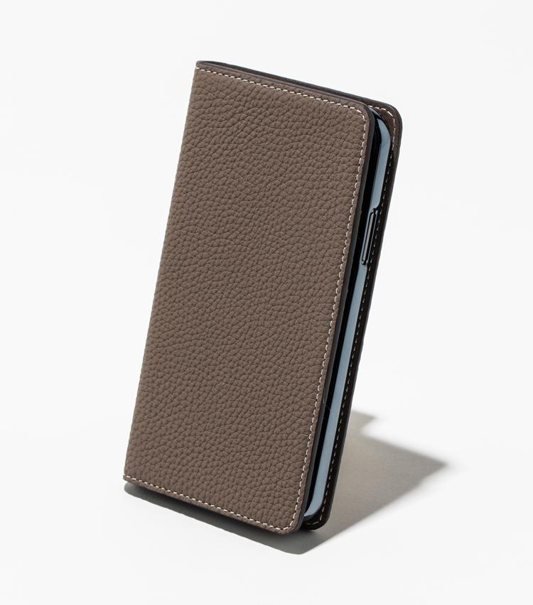 <p><strong>【人気No.1革小物】<br />ボナベンチュラ iPhoneケース</strong><br /> 適度な厚みと柔らかさが特徴の高品質な牛革を採用したiPhone ケース(Xs、X 対応)。無駄のない横開きタイプの2つ折りケースは、使いやすく大人に最適だ。数ある革小物のなかでiPhone用ケースが一番人気になるのは、いかにも現代的な結果といったところか。1万3000円<br /> <small>※撮影のためにiPhoneを装着しています</small></p>