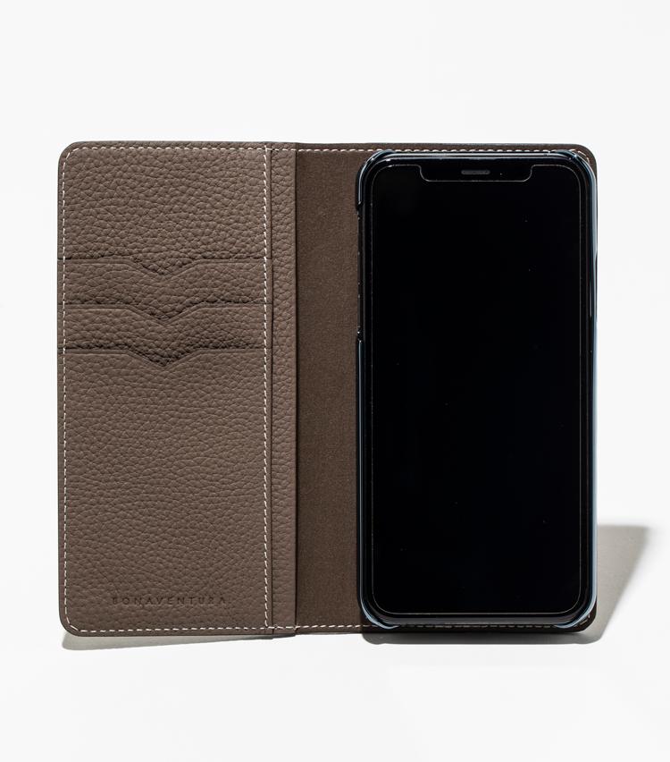 <p><strong>【人気No.1革小物】<br />ボナベンチュラ iPhoneケース</strong><br /> カバーを開くと中にカードポケットが備わっていてICカードなどを収納可能。キャッシュレス化が進む現代では、カードを数枚挿しておけば、財布感覚で使うこともできるのでは。1万3000円<br /> <small>※撮影のためにiPhoneを装着しています</small></p>
