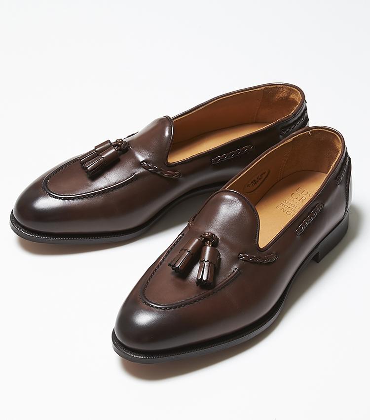 <p><strong>BELGRAVIA</strong></br>やや細身でストレートなシルエットがエドワード グリーンらしいドレス感を放つタッセルローファー。よくあるタッセルとは違い、タッセルの紐部分が編み紐、モカ部分とヒールに施されたつまみ縫いの表情と相まって、存在感たっぷり。靴に立体感が出るだけでなく、装飾としてもラグジュアリーさが際立つ。ローファーに多く採用されているラスト「184」は、程よいラウンドトウで英国的な雰囲気を携える。スーツやジャケパンなどドレッシーな装いの足元にもよく映える。16万3000円(エドワード グリーン 銀座店)</p>