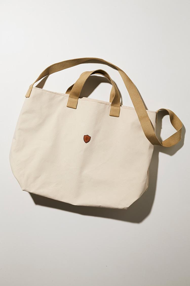 <p><strong>フェリージ</strong></br><br /> シルクのように上品な光沢を放つナイロンと、トスカーナのバケッタレザーを組み合わせたフェリージのビジネス鞄は、M.E.世代のビジネスマンにはマスターピース的な存在。それは休日カジュアルにおいても然り。こちらのキャンバス生地のトートバッグは、コットン綿糸を平織りした厚手の帆布。ナチュラルな風合いがありながらも、強度があり摩擦にも強く、見た目以上に軽いのが特徴。間口は革紐により開閉が可能。内側にはオープンポケットが一つ備わり、使い勝手も◎。縦42×横43×マチ21㎝。4万5000円(フィーゴ)︎</p>