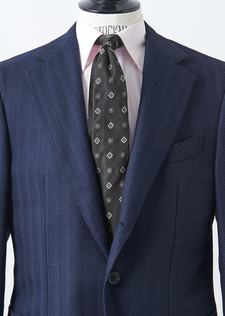 <p>ネイビースーツに黒ベースの小紋タイも、紺地のネクタイと比べると少しモードでシャープな印象に。ここに艶感をプラスするなら淡いピンクなどのカラーシャツを合わせてみよう。<br /> </br><small>ジャケット14万5000円/カルーゾ(シップス 銀座店 TEL:03-3564-5547)、シャツ2万5000円/バグッタ、タイ2万7000円/トゥモローランド(以上トゥモローランド TEL:0120-983-522)</small></p>