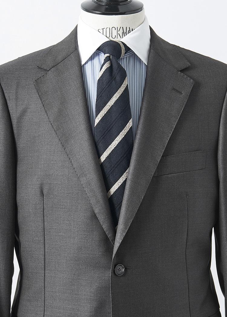 <p>無地スーツをシャープに見せるなら、極細のストライプクレリックシャツに、ピッチ広めの黒地ストライプタイでまとめてみよう。<br /> </br><small>スーツ15万円、タイ1万8000円/以上マッキントッシュ ロンドン(SANYO SHOKAI カスタマーサポート TEL:0120-340-460)、シャツ2万9000円/ポール・スチュアート(ポール・スチュアート 青山店 TEL:03-3406-8121)</small></p>