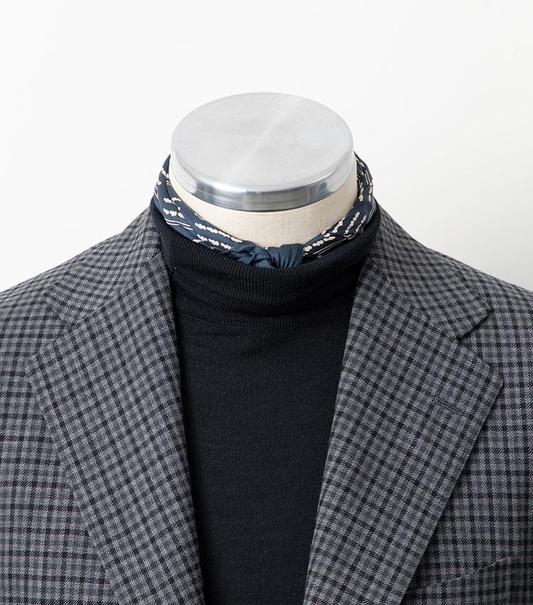<p><strong>【Technique 2】柄スカーフ(チーフでも可)をIN</strong><br />スカーフをプラスしてアクセントをつけてみるのもいい。ただし、タートルネックの上からスカーフを結ぶと結構派手に見えるので、ニットの内側でスカーフを結び、少しだけ覗かせるくらいがおすすめだ。写真ではわかりやすいよう多めに覗かせているが、首元の結び目付近だけを覗かせて、後ろの方はニットで隠してしまってもよい。スカーフは無地でも悪くないが、色柄もののほうがアクセントとしての効果は高い。スカーフを持っていないという方はチーフでも代用可能。こちらの写真でも、45㎝四方のシルクチーフを使用している。</p>