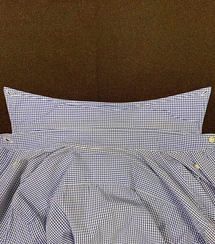 <p>まず、襟を伸ばしてこのような形に。改めてよく見ると、シャツの襟は「襟羽根」と呼ばれるパーツと背中の間に細い帯状のパーツがあることがわかる。これが「台襟」と呼ばれるものだ。</p>