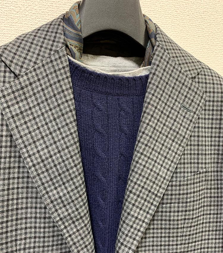 <p>ニットの下にTシャツをレイヤードしたときは、よりシンプルなスカーフ使いをするのもよい。こちらはスカーフを結ばずに、端をニットの中に収めている。</p>
