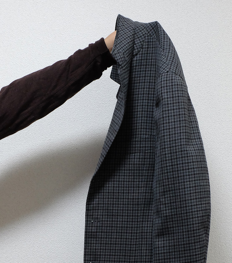 <p>ジャケットを畳む時、一番気をつけなければならないのがラペル周りの型崩れ。これを防ぐため、まずはジャケットの上襟を立ててから畳んでいく。</p>