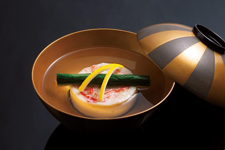 <p>蟹真丈の煮物椀。真丈は魚のすり身に卵白、山芋、豆腐を合わせた地に蟹身を合わせ、松葉柚子の香りと彩りをアクセントに。</p>