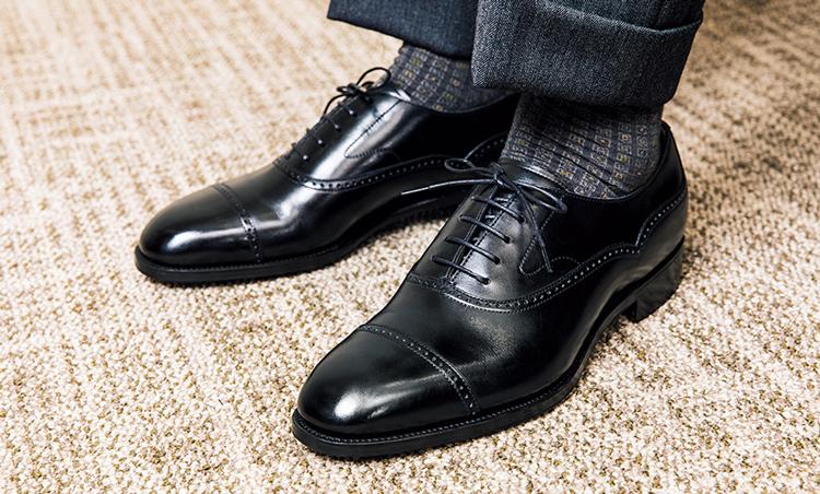 <p><strong>セミブローグでほんのり華やか</strong><br />正統派なスーツの着こなしには、黒のドレス靴が必須だが、クォーターブローグにすると、硬派なストレートチップより少しだけ華が生まれるのだ。</p>