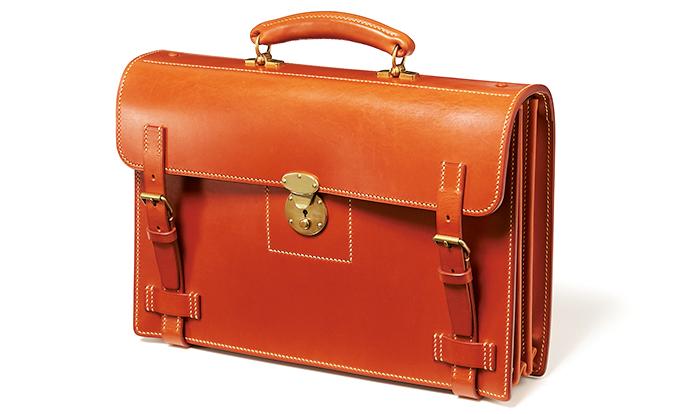 <p><strong>【BK41 ブライドルカカエ鞄】<br /> 英国伝統の意匠を芸術へと昇華させた逸品</strong><br /> スタイルは古典的英国調、作りはフジイクオリティ。最上級4mm厚ブライドルレザーの味わいに、あえて太い糸を使った手縫いや真鍮の錠前がニュアンスある表情を添える。ジャバラマチや包みタイプのハンドルも超絶の出来。縦28×横41×マチ10cm。45万円(フジイ)</p>