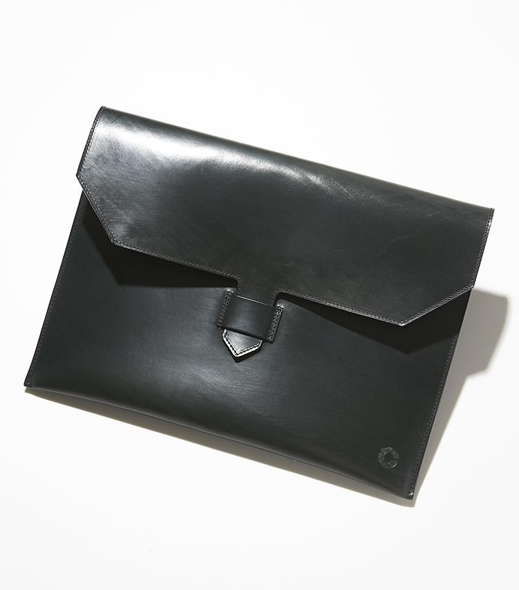 <p>クルーツ</strong></br><br /> 1970年代から、英国のノースヨークシャー州モールトンで熟練職人たちが伝統あるレザークラフトを作り続けるクルーツ社。丁寧になめされた英国伝統のブライドルレザーの1枚革を贅沢に使用。丈夫で肉厚なブライドルレザーを使用しており、薄マチのシャープな作りはドレッシーなスーツスタイルを引き立てる。長年使用してもへたりにくいのが特長。縦26.5×横36.5×マチ3㎝。3万8000円(ヴァルカナイズ・ロンドン)︎</p>