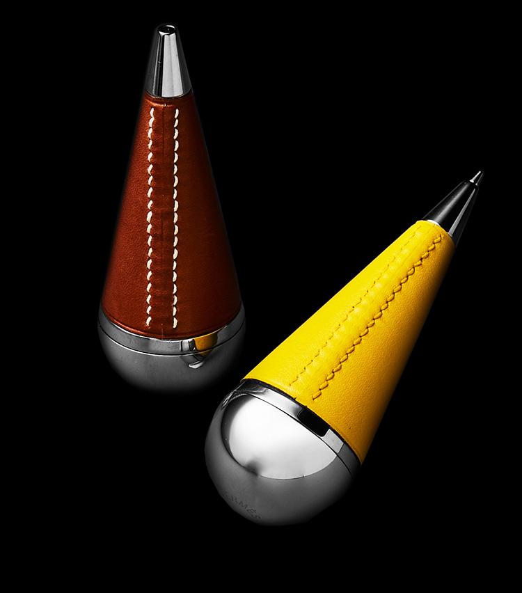 """<p><strong>「キュルブト」</strong><br />1985年~2000年代初頭に展開されていたボールペンを革巻きのデザインで復刻したもの。「キュルブト」とはフランス語で""""起き上がりこぼし""""の意味で、その名のとおりポンと置くだけで自然に立ち上がるようになっている。ユニークな見た目だが、実は手に持ったときのフィット感も非常に良好で、筆記具としての機能性にも優れている。各10万4000円</p>"""