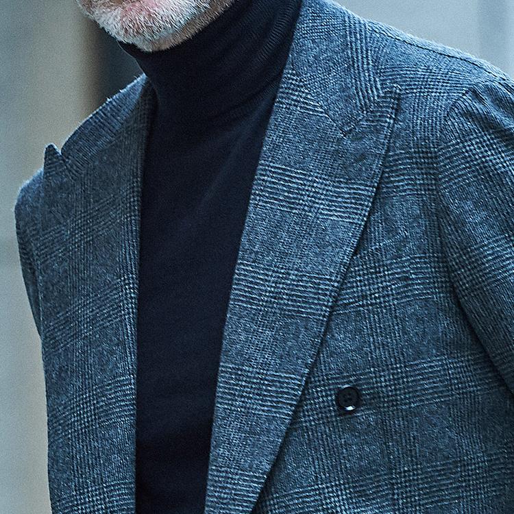 <p><strong>2位<br />「ノータイのスーツ」をきちんと見せるには?</strong><br />スーツをノータイで着るとき、きちんとした印象に見せるには? ドレスシャツをノータイで着ると少し間延びした印象にもなりがち。そこでおすすめなのが、ハイゲージのタートルネック合わせだ。色は濃色のほうが顔周りが引き締まって見える。写真のようにスーツがグレーのグレンチェックなら、同系色の黒無地ハイゲージタートルなどは非常に相性が良い。</p>