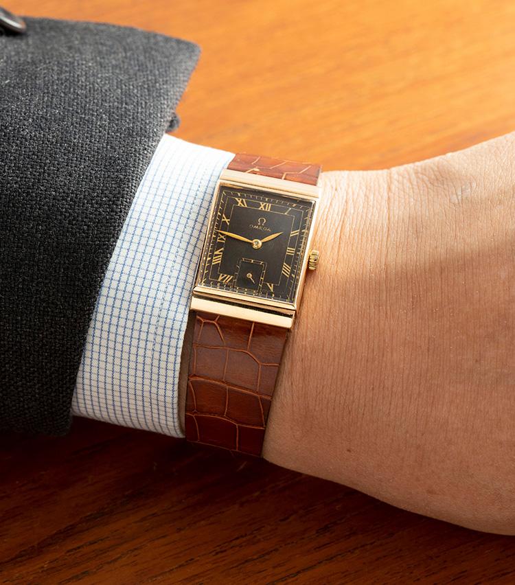 <p><strong>オメガ 1949年</strong><br />ブラックミラーダイヤルにゴールドプリントのインデックスをあしらった色気のあるデザイン。経年によって文字盤が美しいブラウンに変化しており、雰囲気たっぷりの表情になっている。キリリと端正なレクタンギュラーシェイプも魅力的で、ドレッシーなスーツスタイルに相性抜群。小ぶりながら確かな存在感を放つ一本だ。縦30×横21mm。32万8000円</p>