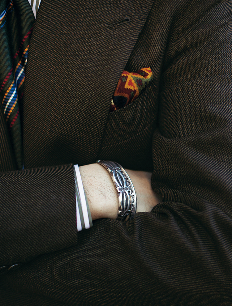 <p><strong>「仕立てのスーツにネイティブアクセがマイ定番です」</strong><br /> アーモリーとは別に、ヴィンテージウォッチ&アクセサリーショップも共同経営するジャン。クラシックなテーラードと同じくらい、ネイティブアクセも愛好しているという。「今日はリヴェラーノで仕立てたブラウンスーツに合わせてみました。こんなミックススタイルは以前から実践していますね」。よく見るとシャツの縞色、帽子、ネクタイの色を揃えていたりと細部まで計算された装いだ。</p>