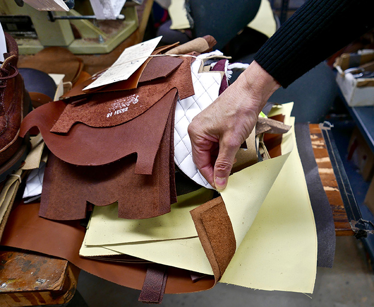 <p>The upper assembly station where the quarters are stitched to the vamp; backstays, collars and eyelet facings are all attached and stitched into place.  In this photo a pair of snake proof boots are to be assembled.  The off-white fabric is 'Turtleskin.' a Kevlar fabric which is impervious to snakebites.  Snake proof boots are popular in the southern United States where snakes are prevalent .<br /> 甲の部分を縫い合わせるステーションでは、つま革に、かかと部分、カラー、アイレットの化粧面などが組み合わされ、縫い合わされます。この写真では、蛇から足を守るブーツが組み合わされています。オフホワイトの生地は、蛇にかまれても耐えられるケブラ生地の「タートルスキン」です。蛇の多いアメリカ南部では、防蛇のブーツが人気があります。</p>