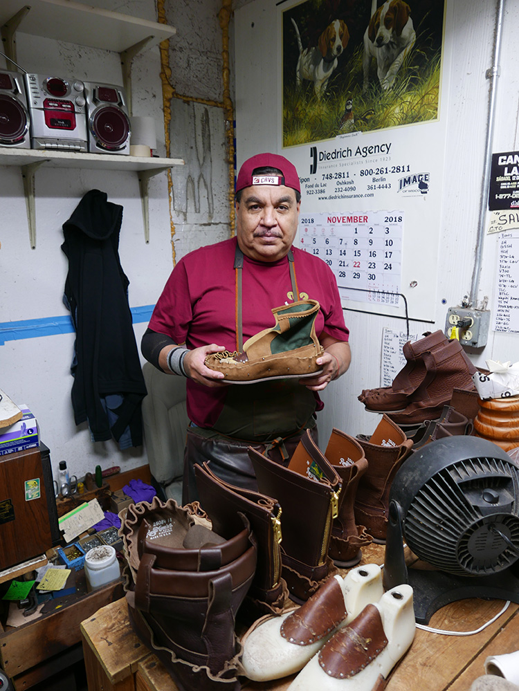 <p> Custom lasts in the foreground which have been built up by tacking leather, in this case,  to the insteps.<br /> The shoemaker is holding a boot with the vamps pulled up and tacked onto a custom last.<br /> この場合は、足の甲に合わせて、革を仮留めして、前面を組み立てているカスタムの木型。靴職人は、ブーツのつま革を引き伸ばして、カスタムの木型に合わせています。</p>