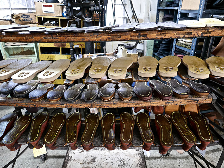 <p>Boots dry on a rack for one day after being soaked in water and having the vamps pulled up and tacked to the last.  When the leather dries it will form perfectly to the custom last.<br /> 水に浸し、つま革を木型に合わせて引き伸ばした後、ラックの上でブーツを丸一日乾かします。革が乾く際に、完璧に木型に沿って形ができあがります。</p>