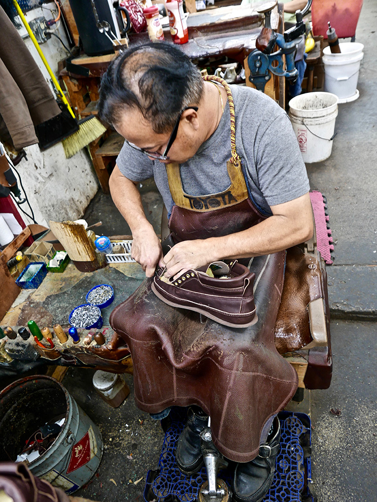 <p>Excess leather being trimmed from the molded vamp<br /> つま革の余分な革をトリムします</p>
