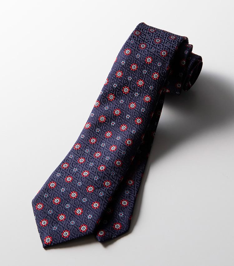 <p><strong>織り柄×フラワー</strong><br />イタリアのネクタイにおいて最も伝統的なモチーフである花小紋も、グッチにかかれば刺激的な柄に。ベースには″G″の複雑な織り柄をあしらい、花柄も大きめに配している。レトロな趣きも備えたミステリアスな表情が魅惑的。2万4000円</p>