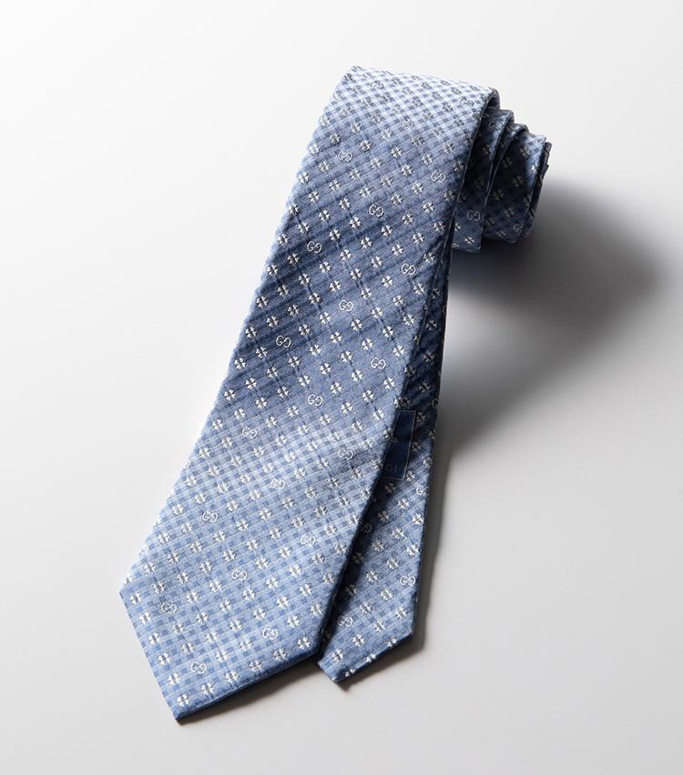 <p><strong>クローバー×ダブルG×チェック</strong><br />チェックの地紋にクローバーとダブルGモチーフをミックスして配置。美しいシルクの光沢感と爽やかな配色が春にぴったりな一本だ。小柄のためコーディネートの幅が広く、柄物のスーツやジャケットにも使いやすい。2万4000円</p>