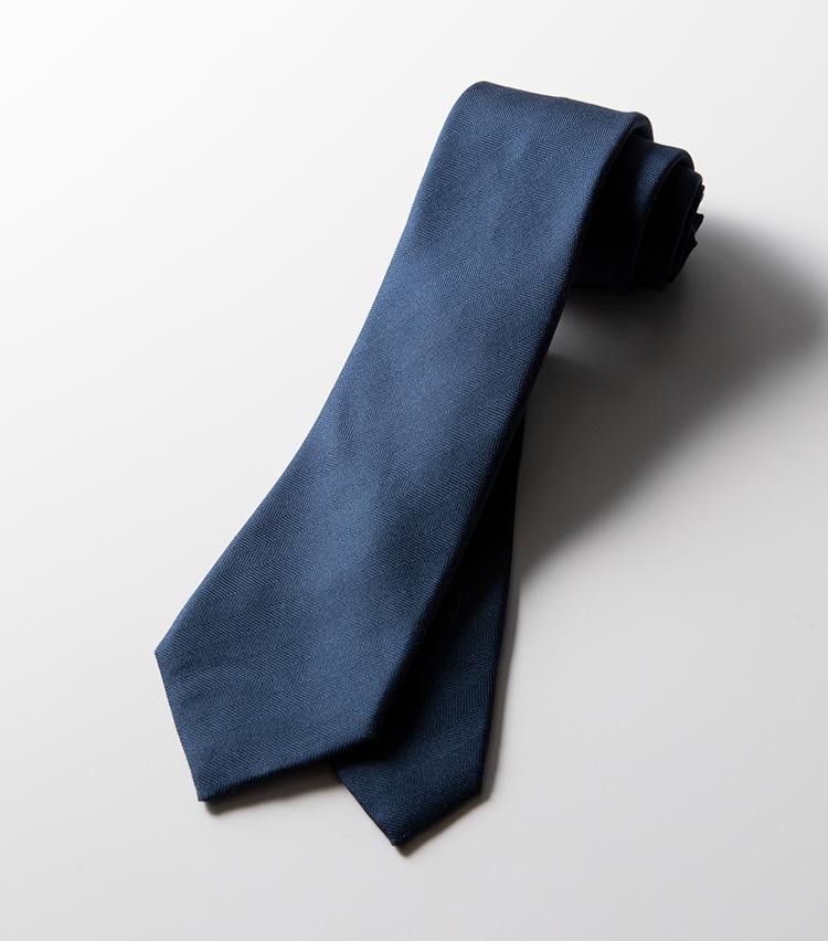 <p><strong>ヘリンボーン織り</strong><br />一見ベーシックな紺無地だが、よく見ると表情のあるヘリンボーン織り。ツイルなどよりもマットな発色が落ち着いた印象だ。さらに印象的なのは、刺繍で表現された馬のモチーフ。一筆書きのタッチがアーティスティックだ。4万6000円</p>