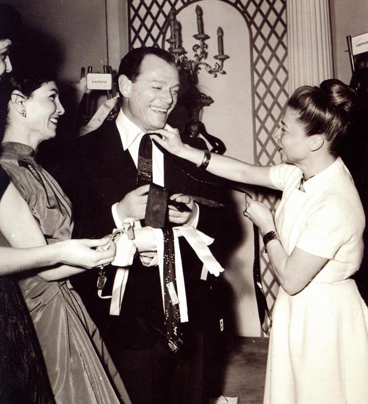 <p><strong>1957年</strong></p> <p>パリのシャンゼリゼ通りの近くで、有名俳優のエディ・コスタンティーヌにブリューワーのネクタイを見せるオートクチュールデザイナーのカルヴェン女史。</p>