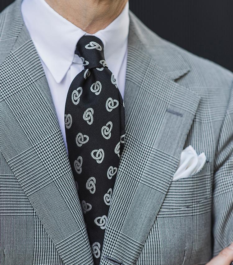 <p><strong>ダブルリング小紋①</strong></p> <p>黒ベースのダブルリング小紋は、大柄グレンチェックに白シャツで、モノトーン合わせが◎。白シャツは、タブカラーやラウンドなどの襟型のほうが洒落感UP。スーツが無地だとタイの柄が目立ちすぎるが、これくらい大柄のチェック柄だと柄のバランスのまとまりがよくなる。</p>