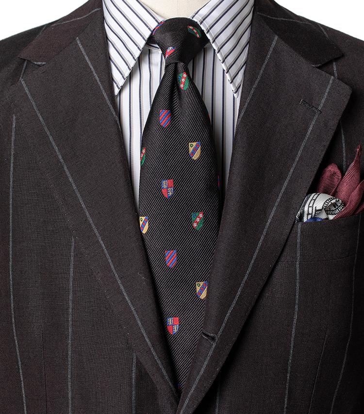 <p><strong>クレイジークレスト柄②</strong></p> <p>紺ブレでシックにまとめた①に対し、こちらは黒のクレストを主役にした「柄×柄×柄」のコーディネート。こげ茶ベースにグレーのワイドストライプスーツ、ネイビーとベージュのストライプシャツを合わせた。こうした派手柄のネクタイの場合、シャツやスーツの柄の幅や色を調整すると、上手く馴染ませることが出来る。</p>