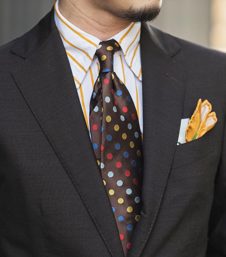 <p><strong>マルチカラードット柄①</strong></p> <p>ドットの一色であるイエローを拾ったストライプシャツに、チーフもイエローをチョイス。シャツとネクタイ、チーフでかなり色を使っているので、スーツはダークブラウンで落ち着かせるのがポイント。</p>