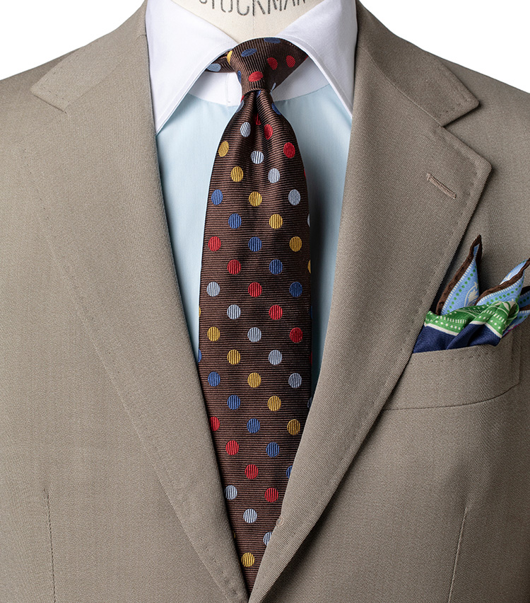 <p><strong>マルチカラードット柄②</strong></p> <p>ネクタイのブラウン基調を生かし、今度はコットンウールのベージュスーツを。ここでもネクタイの色を拾って、白ではなくミントグリーンのクレリックシャツを合わせ、クラシックながら色合いで軽さを出しているのがポイント。チーフにもペールトーンを入れて統一感を。</p>