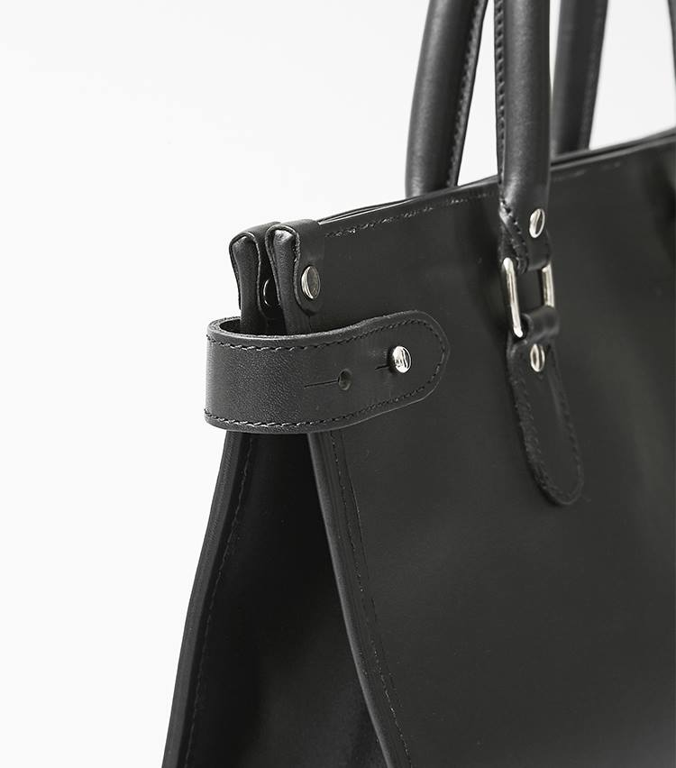 <p>頑丈な持ち手や、縫合部の堅牢さは老舗ファクトリーならでは。上の三角マチ部分は、側面のベルトで止めておくと開口部はスマートに。</p>