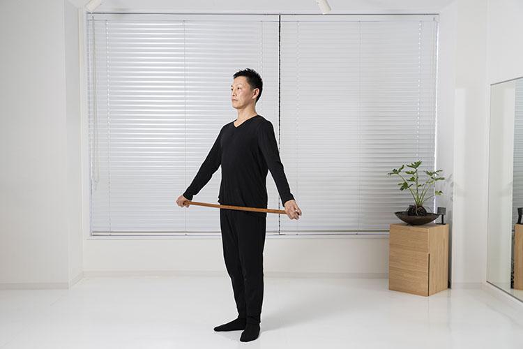 <p>棒の端を持ち、脚を軽く揃えて立つ。肩が硬い人は、できるだけ両手の幅を広くして棒を持つように。</p>