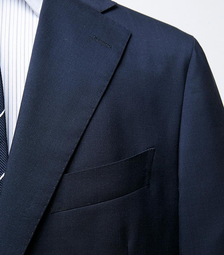 <p><strong>バルカポケット</strong></br>胸ポケットは上に向かってわずかにカーブしている。イタリアのバルカポケットにも通ずるが、こちらはより控えめで都会的な印象だ。ちなみにラペルのラインも直線的すぎず、幅は太すぎず細すぎずのバランスに設定されている。</p>
