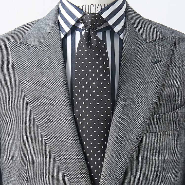 <p><strong>3位<br /> 定番グレースーツを洒脱に見せるには?【1分で出来るスーツのお洒落】</strong><br />手持ちのグレー無地スーツを、いつもよりお洒落に見せるにはどんなシャツ&ネクタイの組み合わせがよいか? 白シャツを合わせてはいつもと変わり映えがしないので、写真のようなグレーの太めロンドンストライプのシャツを合わせてみると胸元に一気に存在感が増す。ここに柄のピッチをずらして、黒地の小さめドットタイをもってくれば柄同士のバランスも◎。色柄をすべて黒・グレー系のモノトーンで統一していることも、シックに見せるポイントだ。</p>