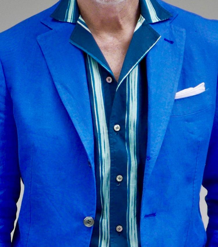 <p><strong>4.シャツ襟で魅せるリゾートらしい開放感</strong></p> <p>滞在先のホテルでディナーを楽しむ。ジャケットはリゾートらしい鮮やかなブルーのリネン混に、トロピカル柄がプリントされた開襟タイプのシャツをコーディネート。シャツの襟先をジャケットからアウトし、ボタンも1つ開けてリラックス気分を演出する。パンツもクリーンで爽やかなホワイトで合わせばマリンなテイストに! 海辺のリゾートで過ごす、上質な大人の時間にふさわしい装いだ。</p>