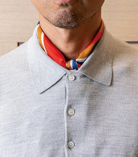 <p>ニットポロの襟元にスカーフを挿す場合、結ぶ、垂らすは、どちらもあり。結ぶなら66cm前後角、垂らすなら87cm前後角を選ぶと上品にキマる。</p>