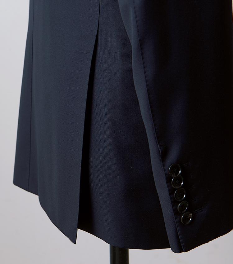 <p><strong>【Check!】長めのサイドベンツ</strong><br /> ジャケットの着丈に比してサイドベンツの切れ込みはかなり深めだ。ちょっとした動きで後ろ裾がたなびき、躍動的な男を印象付ける。高めの位置でシェイプさせたウエストとの相性も最高である。</p>
