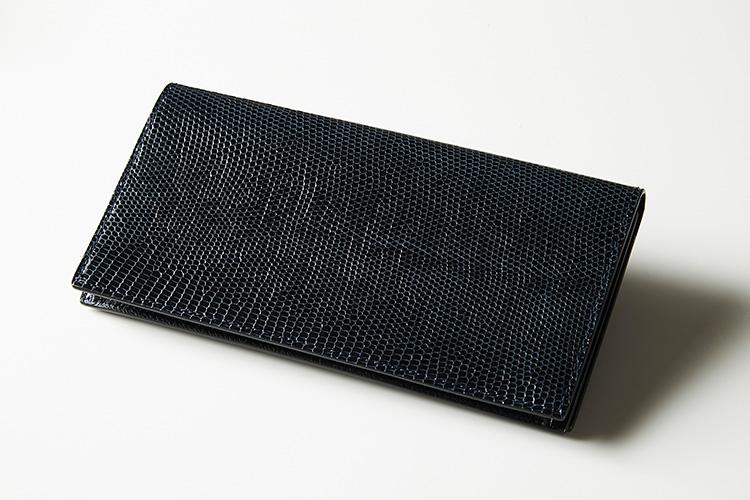 <p><strong>カミーユ・フォルネ</strong></p> <p>マリーン色のリザードで仕立てたコイン室なしのロングウォレットは、小粒の鱗が品良く艶めいてなんともドレッシー。スーツのポケットに入れてもシルエットが崩れにくい薄さで、スマートに持ち歩くことができる。縦9×横18×マチ1.5cm。 17万円(カミーユ・フォルネ銀座本店)</p> <p/>