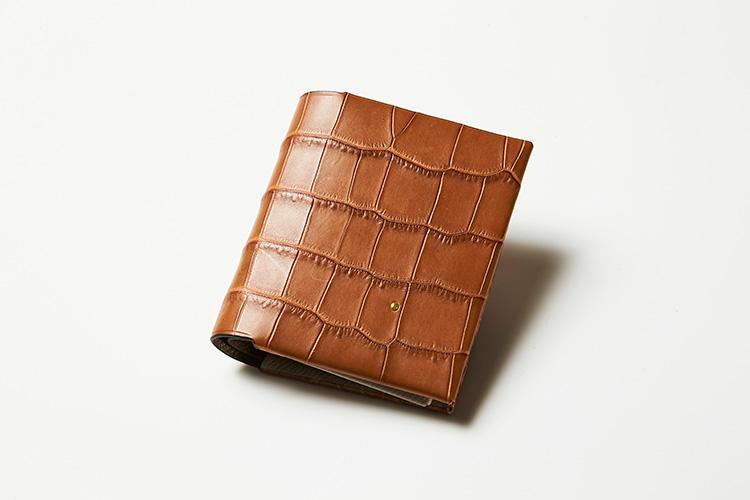 <p><strong>T.MBH</strong></p> <p>縫わずに薄くすいた革を貼り合わせるという独自技術「葉合せ(はあわせ)」による財布は、コンパクトさと大容量を両立。クロコダイルの最高峰、ポロサスクロコダイルレザーには、ブランドアイコンである18金ピンクゴールドの粒がえくぼのように輝いている。縦8.5×横9.5cm。12万5000円(ストラスブルゴ)</p> <p/>