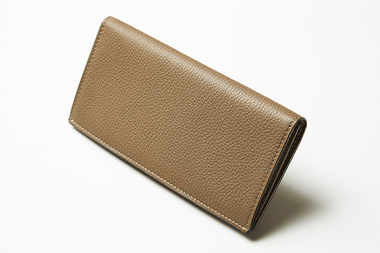 <p><strong>シセイ</strong><br /> 高級感あふれるカーフレザーによる薄マチの長財布は、深みのあるトープカラーと相まって、デスクに置いてもサマになる。ブランドロゴ一切なしの潔いデザインも品がいい。縦8.5×横17.5×マチ1cm。5万9000円(ストラスブルゴ)</p>