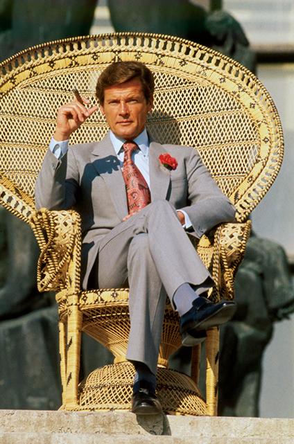 """<p><strong>3代目('73-'85)<br />【Check!】フレア気味のパンツ</p> <p>解説:エレガントでユーモラスな007に相応しい明るく華のあるスーツ姿</strong><br /> しなやかで淡いトーンの生地といい、フレア気味のパンツといいコンチネンタル風のスーツを纏ったムーア。トレンドを貪欲に取り入れた当時の007シリーズらしい""""エマニエルポーズ""""も笑える。</p><figcaption>Photo:Sunset Boulevard/寄稿者</figcaption>"""