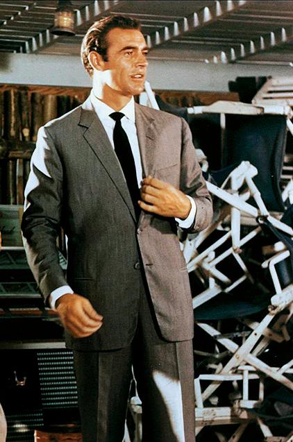 <p><strong>初代('62-'67,'71)<br />【Check!】広い肩に細いラペル幅</p> <p>解説:意外とアメリカンでモダン!タフガイに相応しいスポーティさも</strong><br /> 着用スーツは英国アンソニー・シンクレア製だが、シルエットは米国的でスポーティなボックス型。それがコネリーの逞しい肉体によく似合っていた。かなり細めのラペル幅もモダンな雰囲気を演出。</p><figcaption>ⒸAlamy Stock Photo/amanaimages</figcaption>
