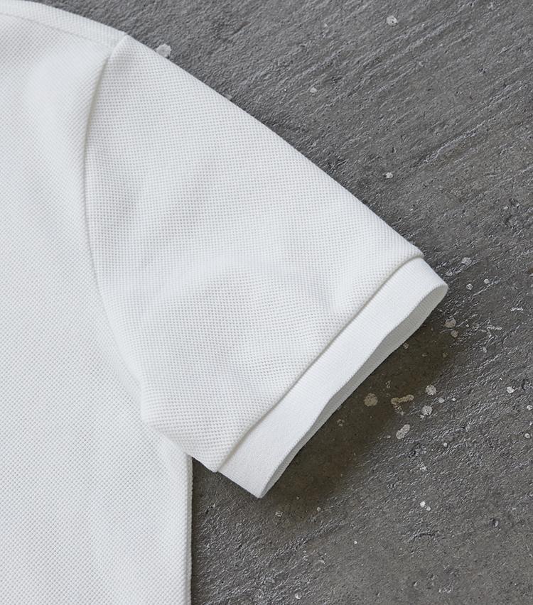 """<p><strong>ジャケットを着ても""""もたつかない""""細腕</strong></br>ちょうちん袖とも称されるラコステ特有のポロシャツ袖を、膨らみを抑えてほっそりアレンジ。そのためジャケットを羽織っても、袖をスッと通しやすく収まりもいい。</p>"""