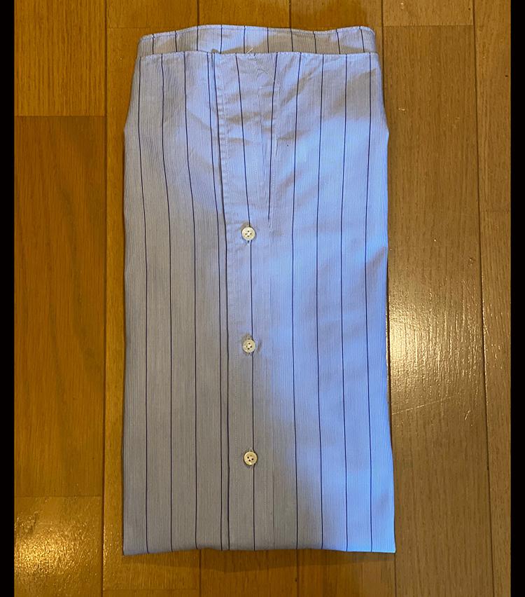 <p>⑦縦長になったシャツを半分に折り畳む。</p>