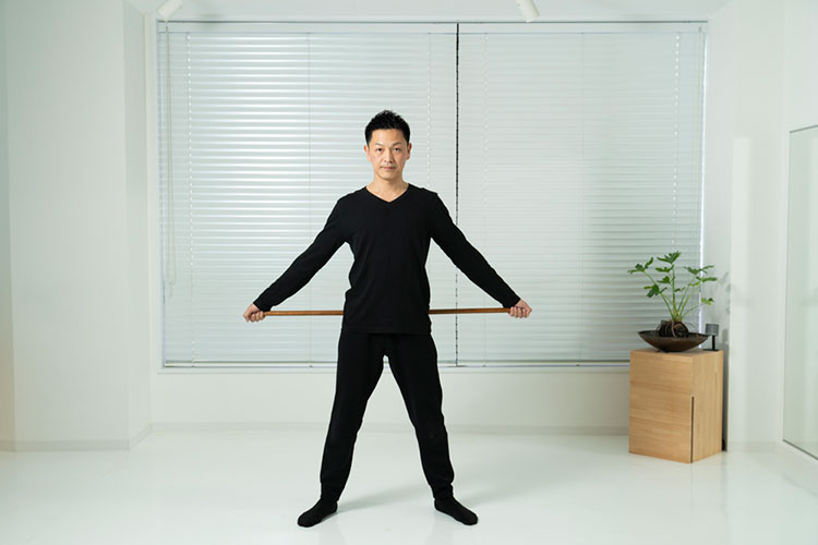 <p>両脚を肩幅に広げて立ち、腰に棒を当てる。</p>