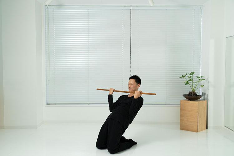 <p>そのまま上体を後ろへ倒しながら、腕を曲げて棒をあごのあたりまで引き寄せる。この時、身体を下腹部で支える。</p>