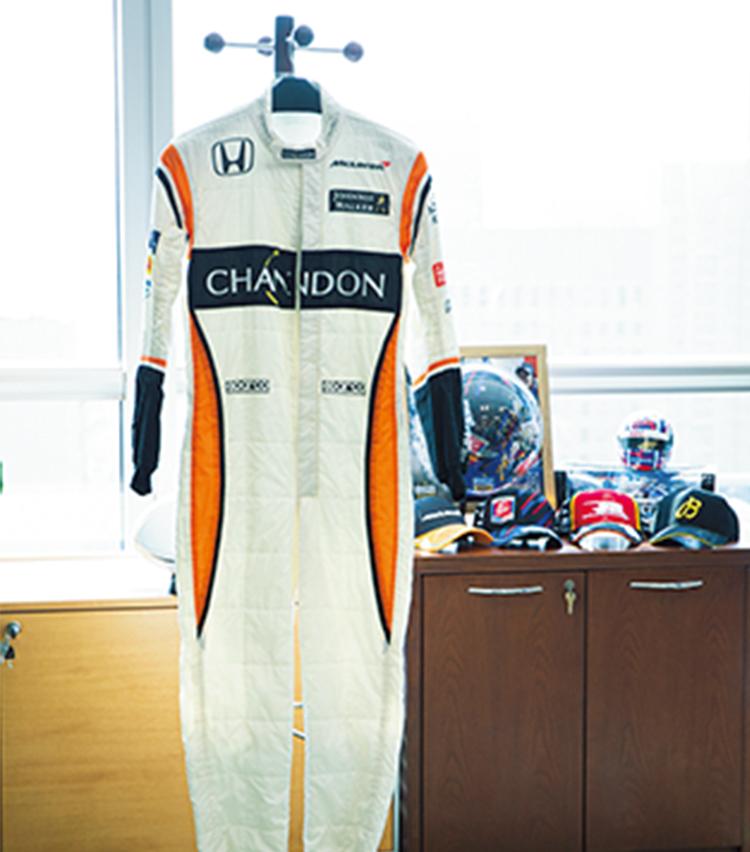 <p>かつては自らステアリングを握っていたほどのモータースポーツファン。執務室にもレーシングスーツが。社内のハロウィンイベントでも着用したと本人談。</p>